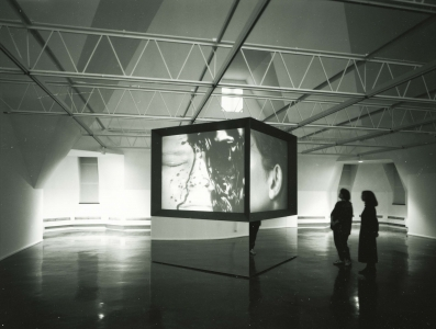 A large cube stands in the gallery, projecting a video of a calm face being covered in a dark liquid.
