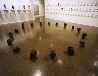 Bronze busts of human heads face each other in a large circle on the floor.