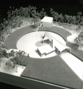 Model of an almost airplane-shaped house with a rectangular extension on one side, with a ring of lawn around it.
