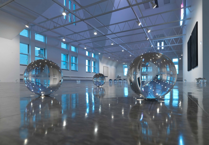 A close-up of small crystal balls on the floor, works hanging around the gallery