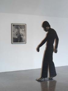 A wooden silhouette, in a walking pose, in front of a print