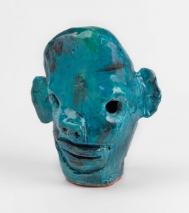 A small blue ceramic sculpture of a head, eyes poked out, tiny holes for nostrils, with splotches of deep red and green paint