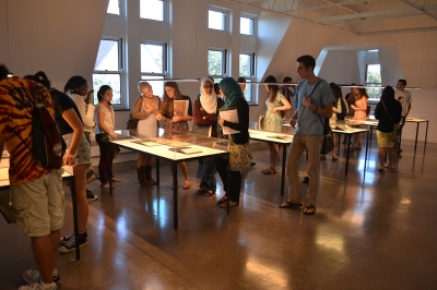 A group of students looks at works displayed on tables under glass.