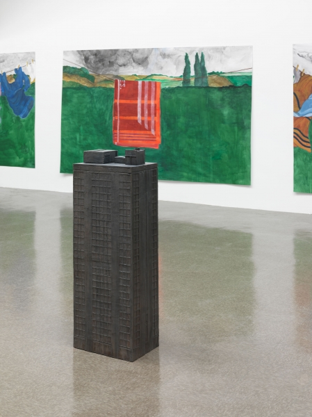 Four bronze sculptures, like tiny obelisks, in front of four watercolor paintings