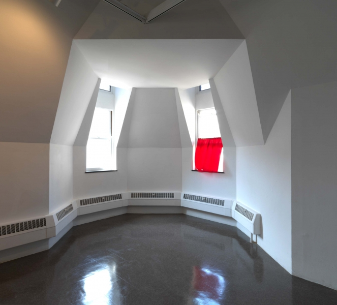 A red curtain covers the bottom half of an open window