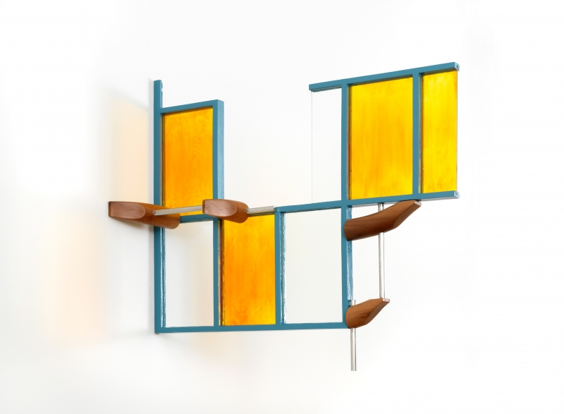 A stand of yellow cherrywood mounted on a wall with a small white, red and aluminum sculpture on top of it