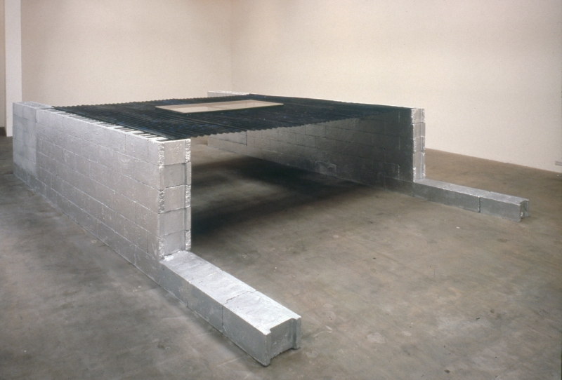 Two lines of concrete blocks rest on the floor, bearing a sheet of steel painted black with two 'feet' of blocks sticking out