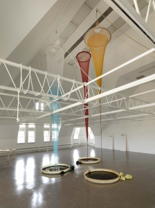 Long blue, red and yellow cloths drape down from the ceiling like condoms into short cups of paint like camera lenses