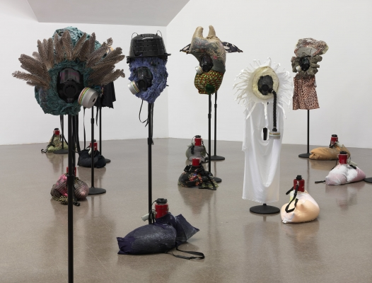 Mixed-media sculptures cover gas masks perched on poles, bags with a megaphone resting at the base of each pole.