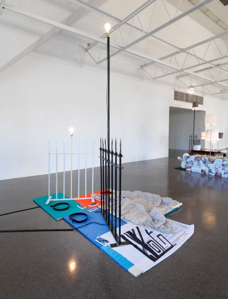 Two playful white sculptures of bears with blue paws sit on rugs covering a reed flute tied with string