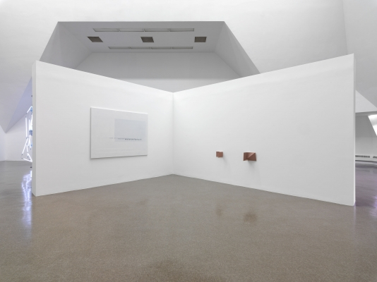 A plain canvas, a section of gray fading to white, mounted near two small bronze sculptures on walls at ninety-degree angles