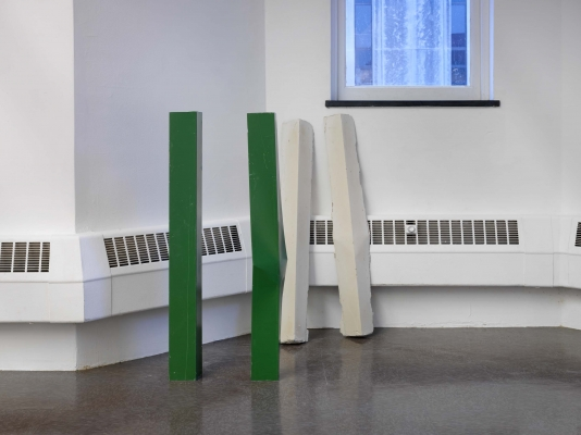 Four metal poles: two green ones stand near the wall, two white lines lean against it