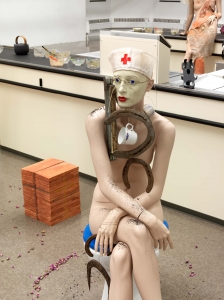 A mannequin sits on a toilet seat, wearing a nurse's hat, with a coffee cup and horseshoes dangling from her neck