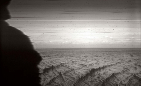 A black-and-white photograph of a sparse landscape, looking onto the horizon, its left edge burnt into a curve