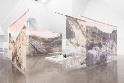 Transparent fabric prints of mountain and desert landscapes with a pink sky around a metal sculpture resting on a platform