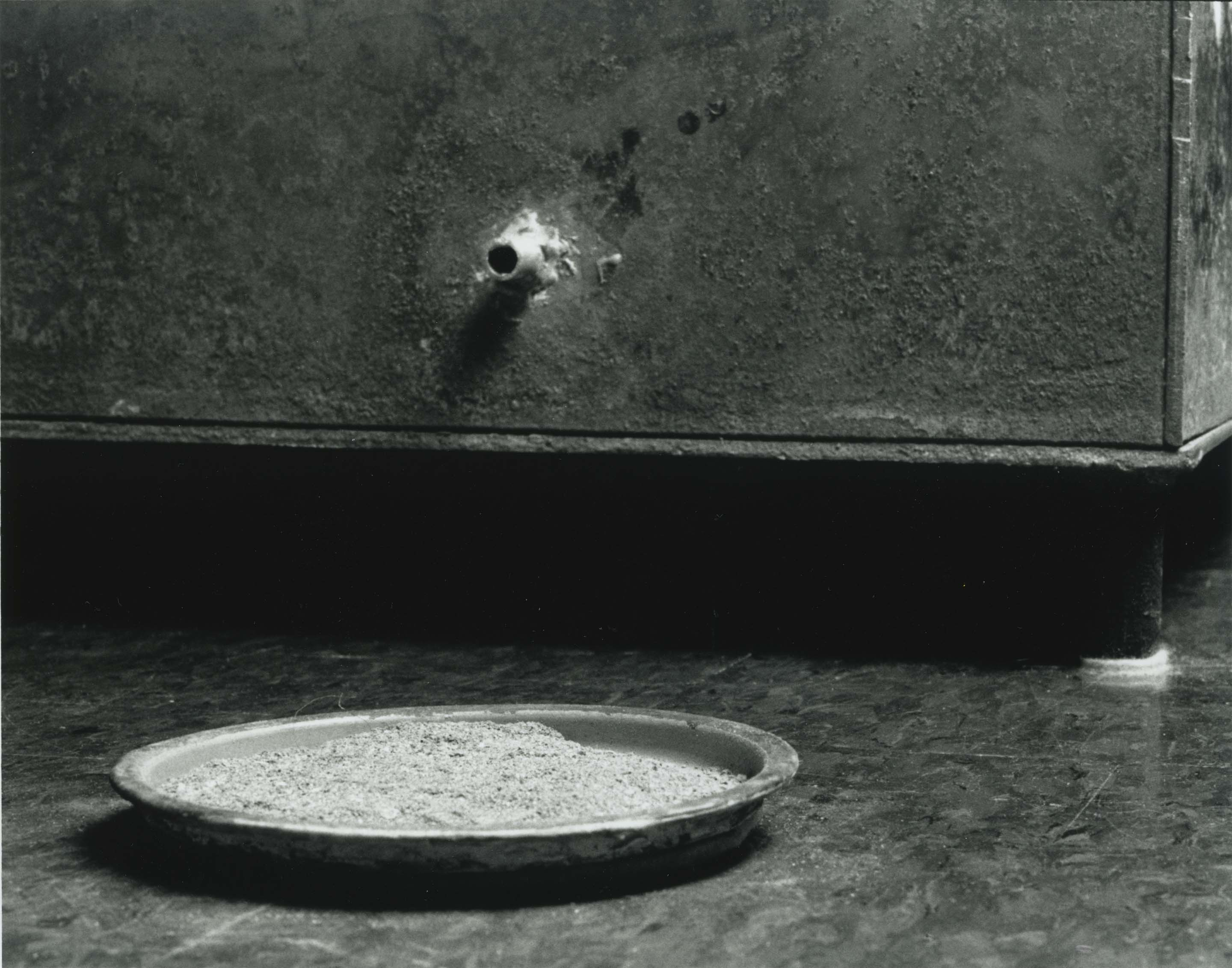 A spigot protrudes from the corner of a large box, opening above a flat dish filled with ashes.