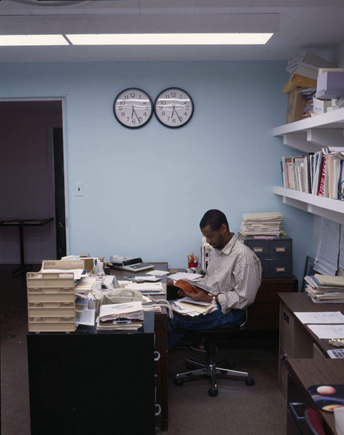 Hamza Walker works at a desk covered in papers.