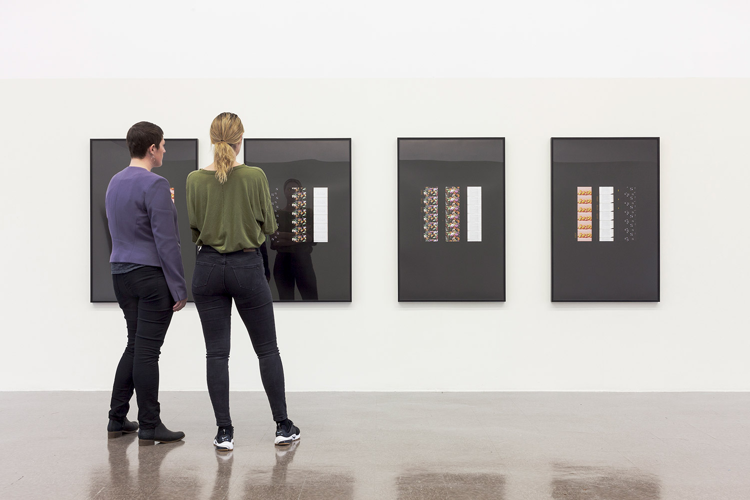 Visitors stand in front of four prints, each with three columns on a black background.