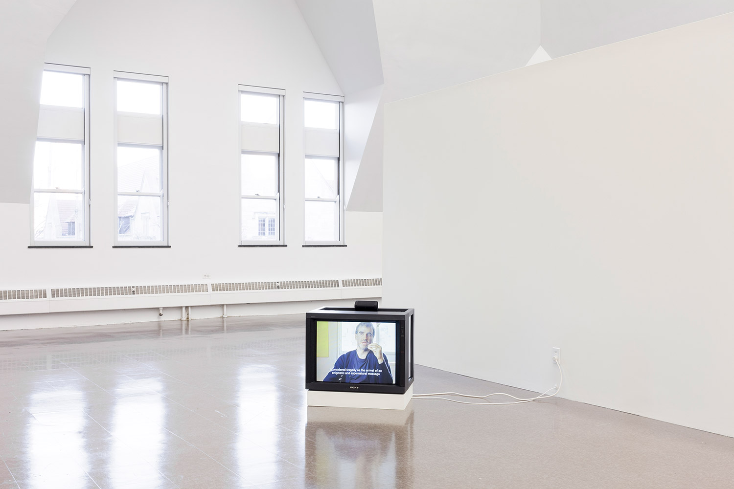 A TV resting on the floor plays a film of a man sitting in front of a window and talking.