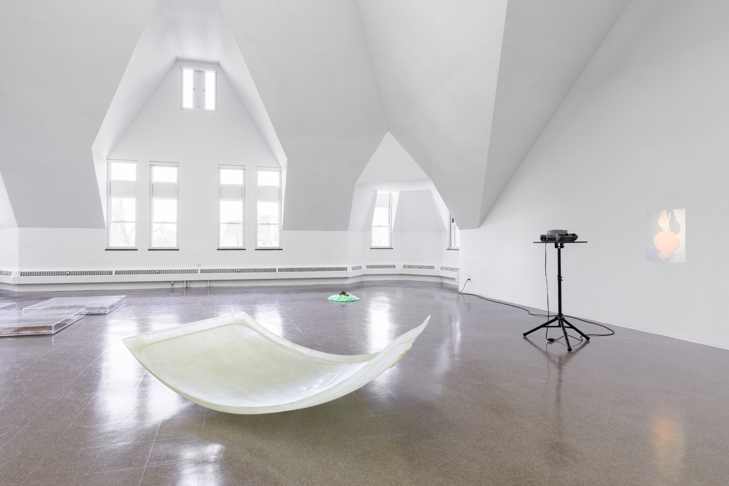 A curved fiberglass sheet rests on the floor near a projector playing a movie on a wall.