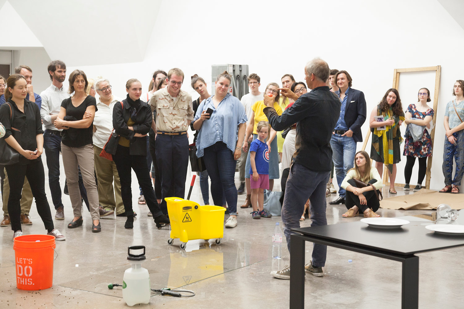 A crowd looks on a man gesticulating in front of them, miscellaneous materials strewn around the exhibition space.