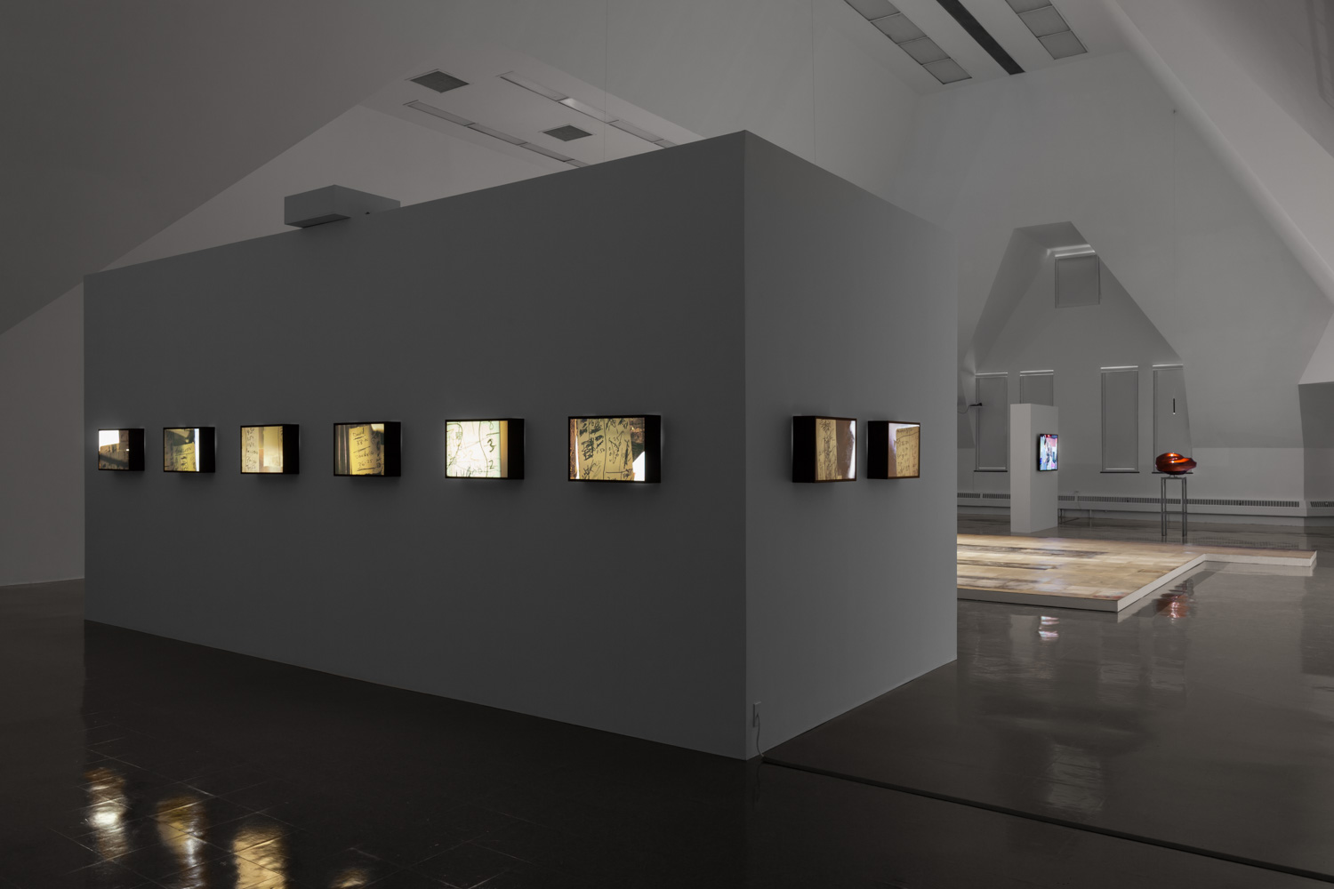 Backlit photographs line a wall, stretching around its right corner, with more works viewable behind.