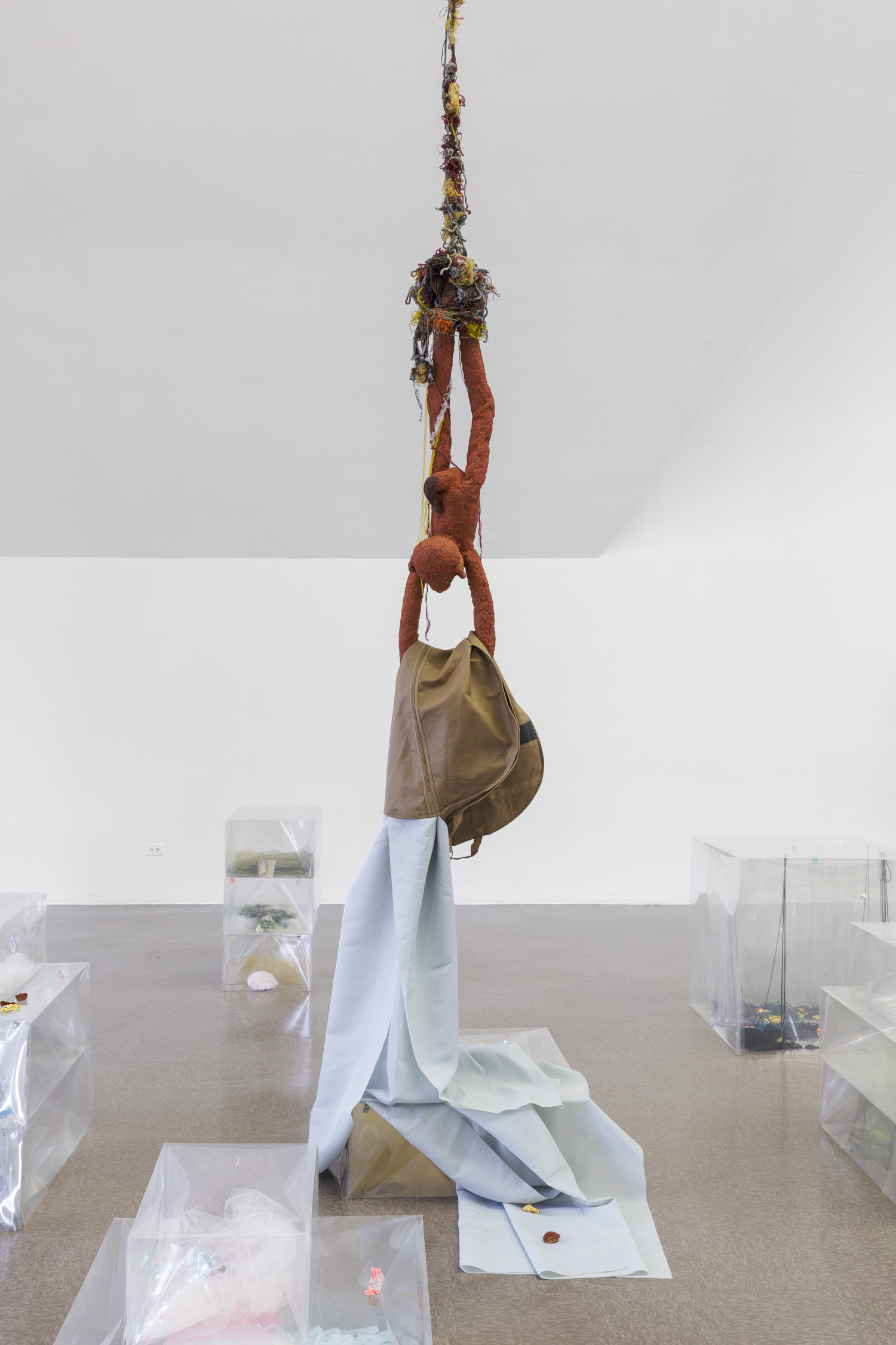Siena rubber figure, legs dangling from a line of yarn suspended at the ceiling, holds cloth in its arms