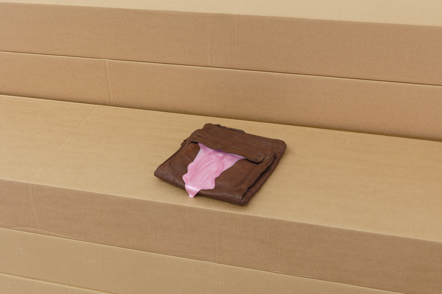 Pink slime oozes out of a brown object resembling a wallet placed on top of cardboard boxes.