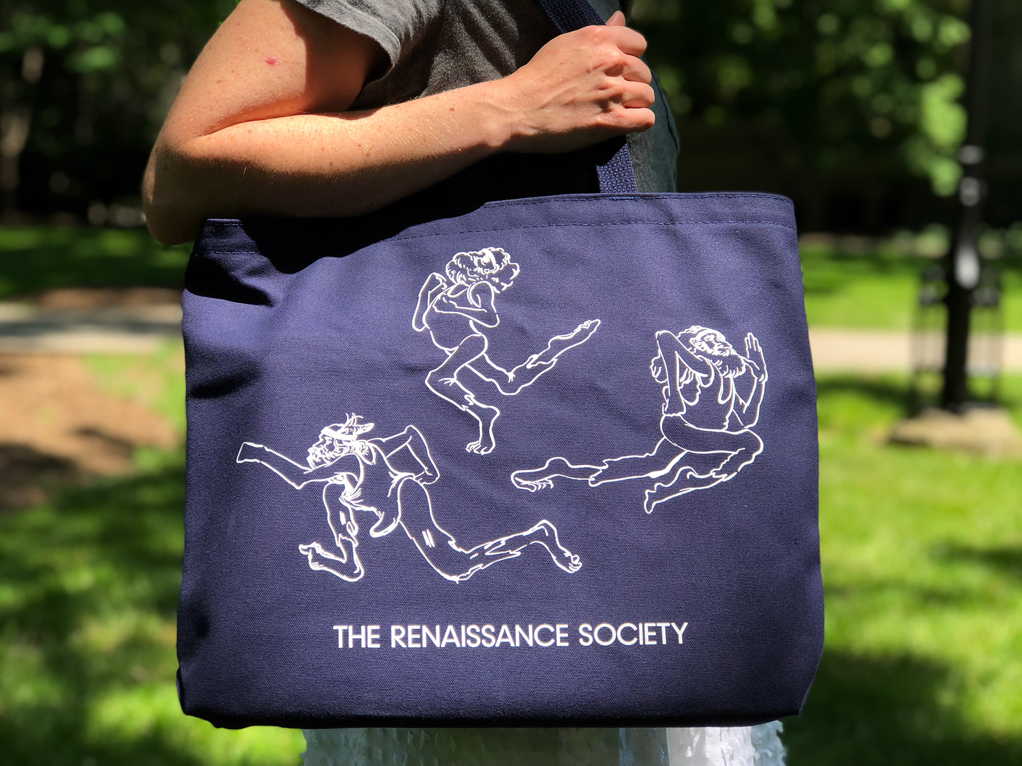 A person holds a dark blue tote bag with white print.