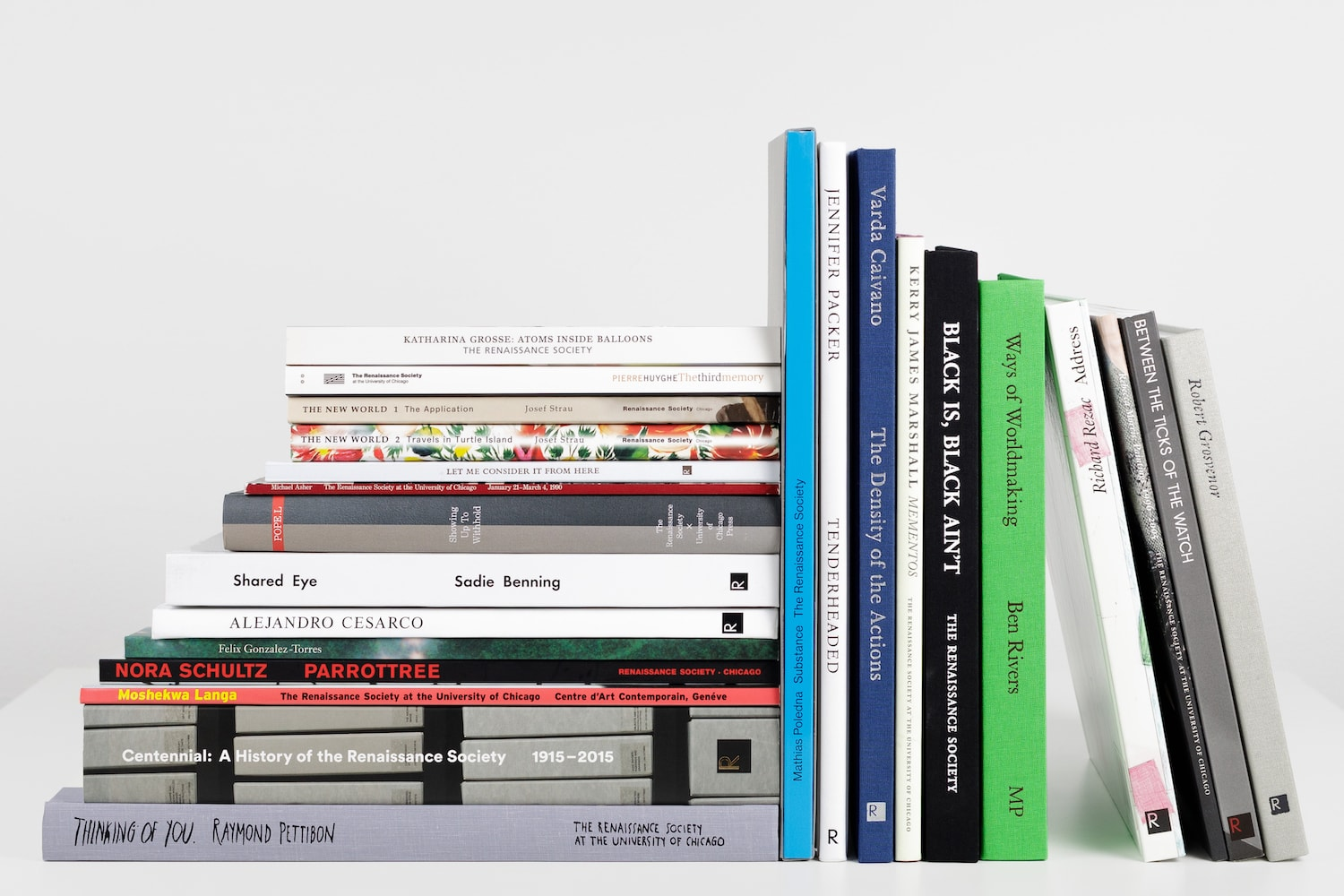 Fourteen books, stacked horizontally, sit next to ten books placed vertically against the stack.