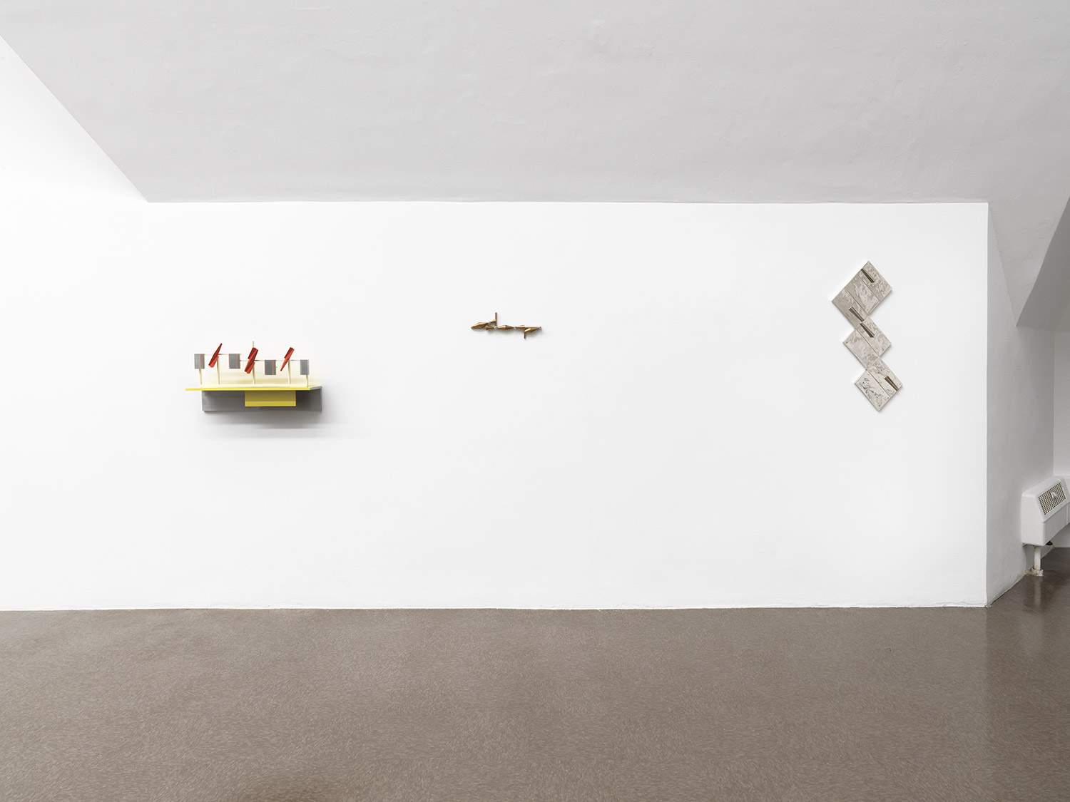 Three small sculptures on a wall, each featuring yellow or silver