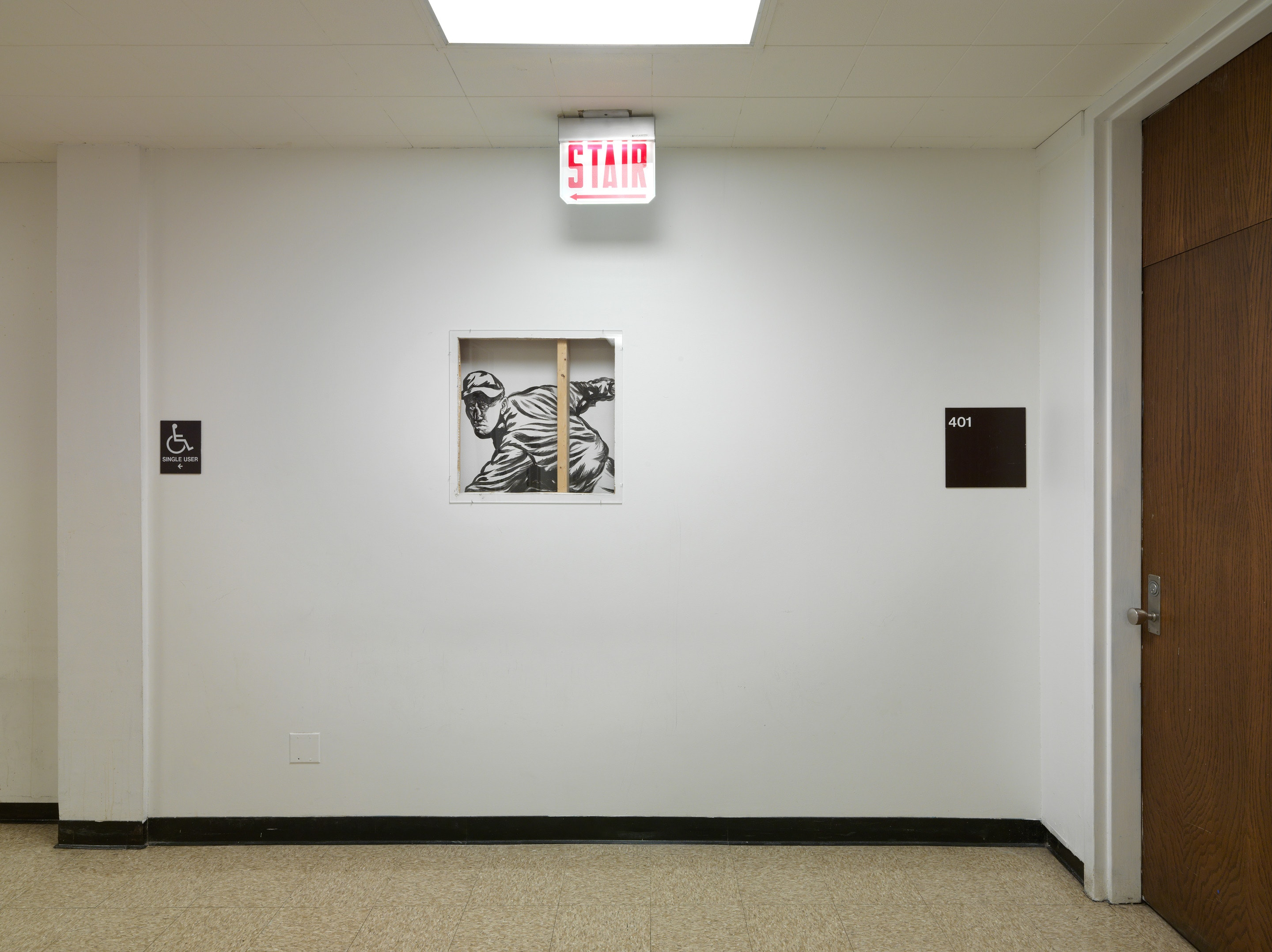 A white wall covers all but one small section of a mural, black-and-white, viewable through a square