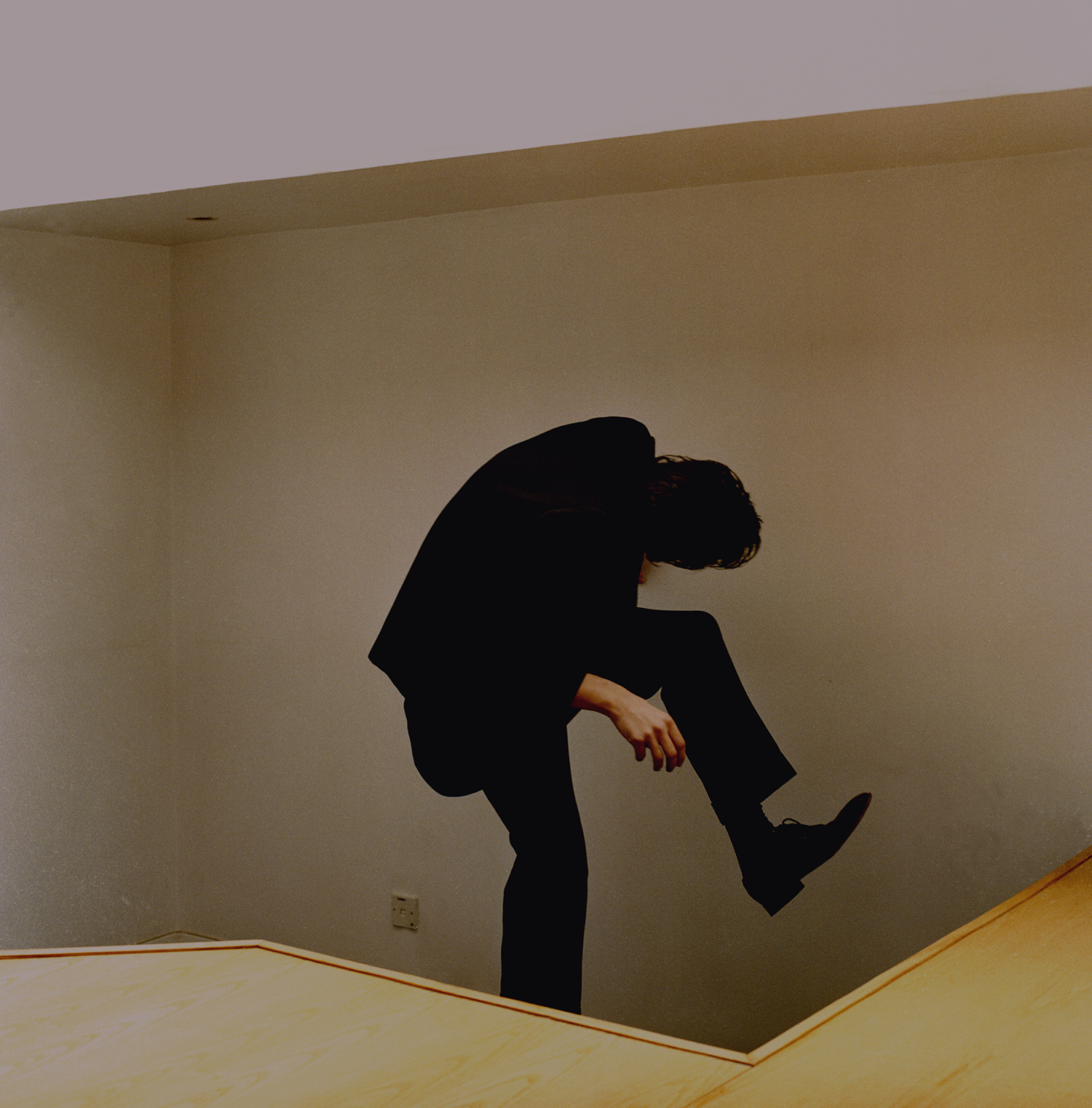A man wearing all black hunches over mid-step, his head turned to the left, between a desk and wall.