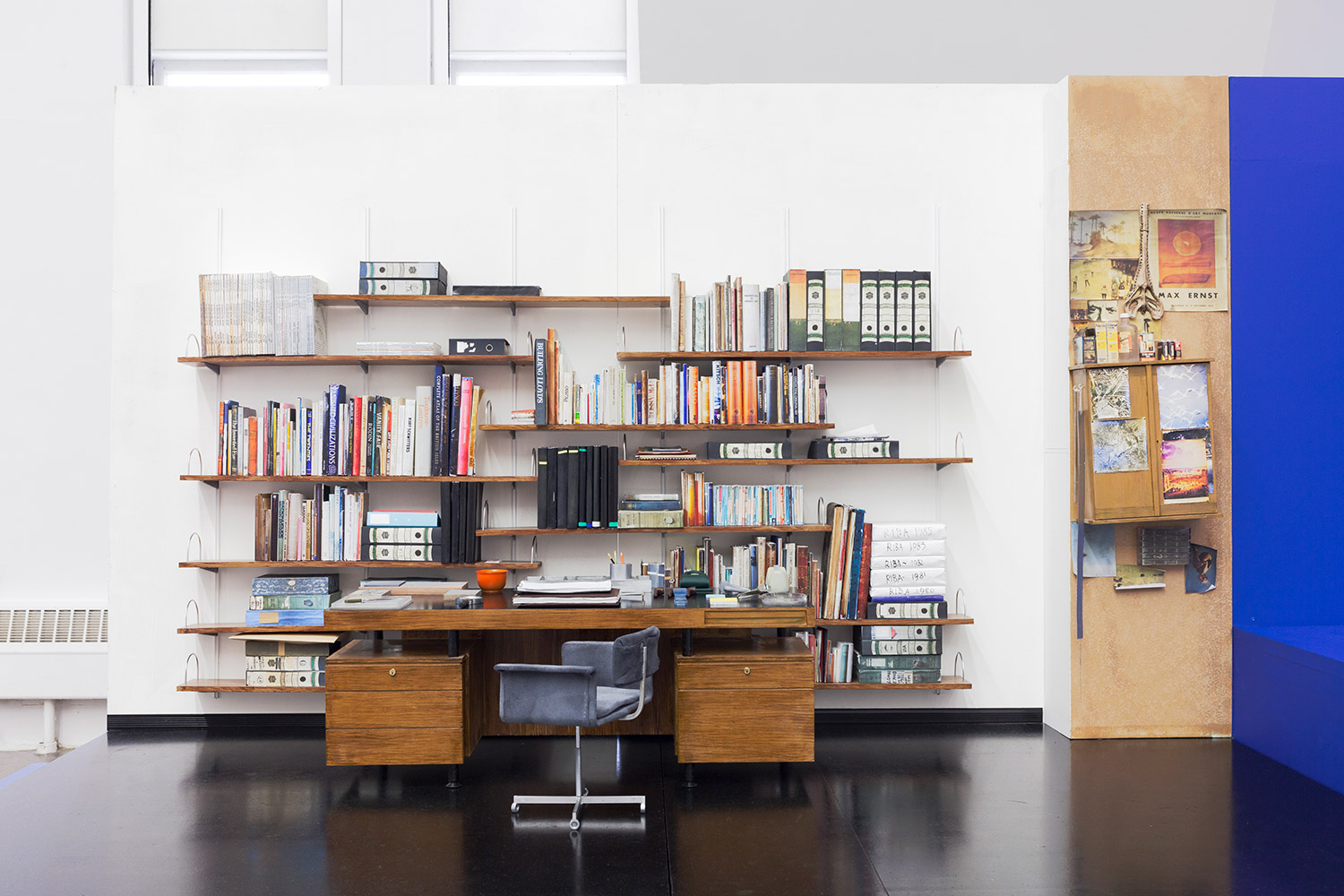 A miniature sculpture of an office desk, with swivel chair, books, hanging works and miscellaneous materials
